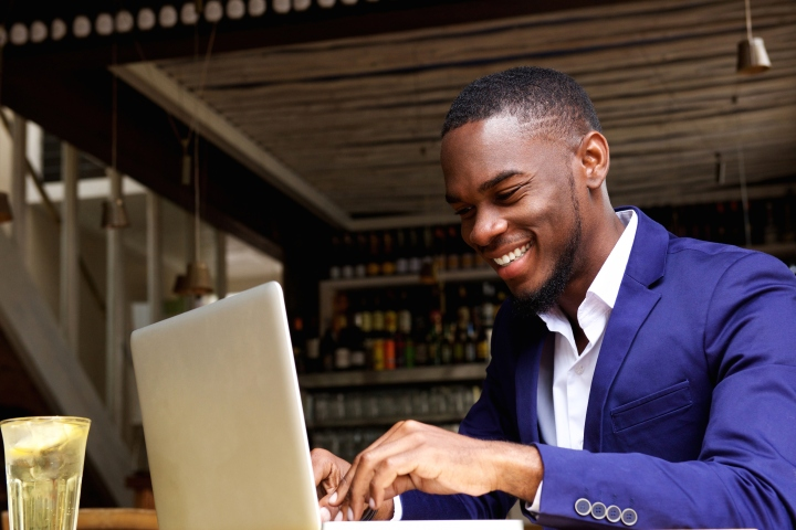 Portrait of smiling african businessman working on laptop at cafe