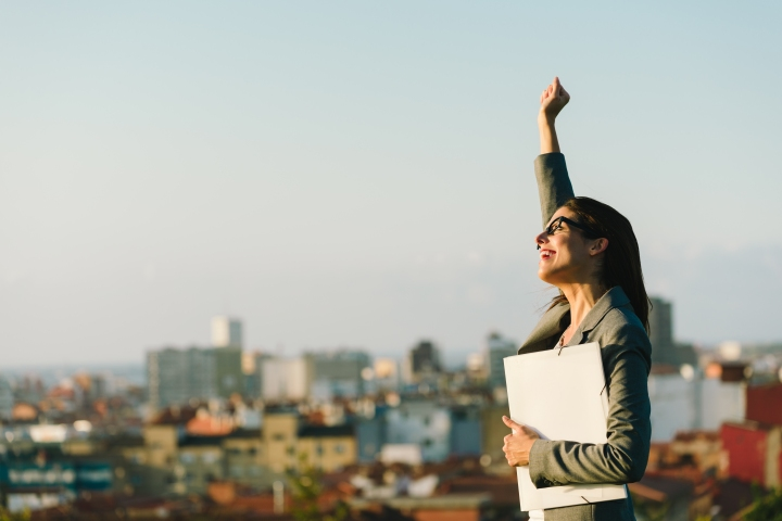 Successful young businesswoman raising arm celebrating business  or job achievement towards city background. Professional happy woman walking outside.