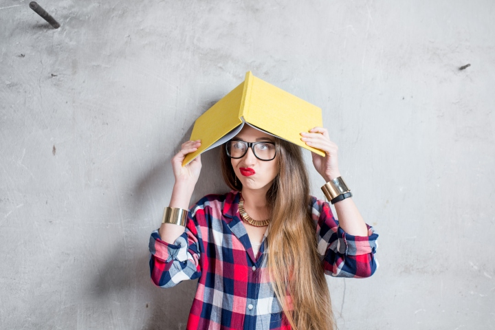 Portrait of confused student in checkered shirt with yellow book on the gray wall background